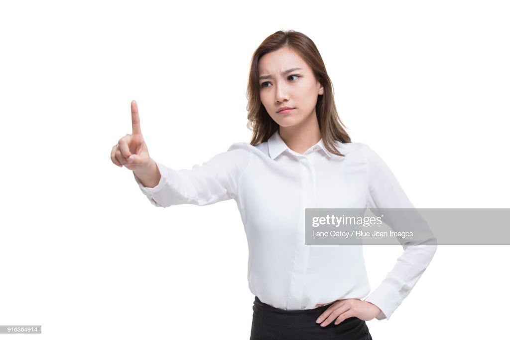 Serious young businesswoman pointing : Stock Photo