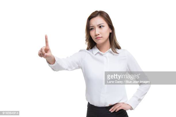 Serious young businesswoman pointing