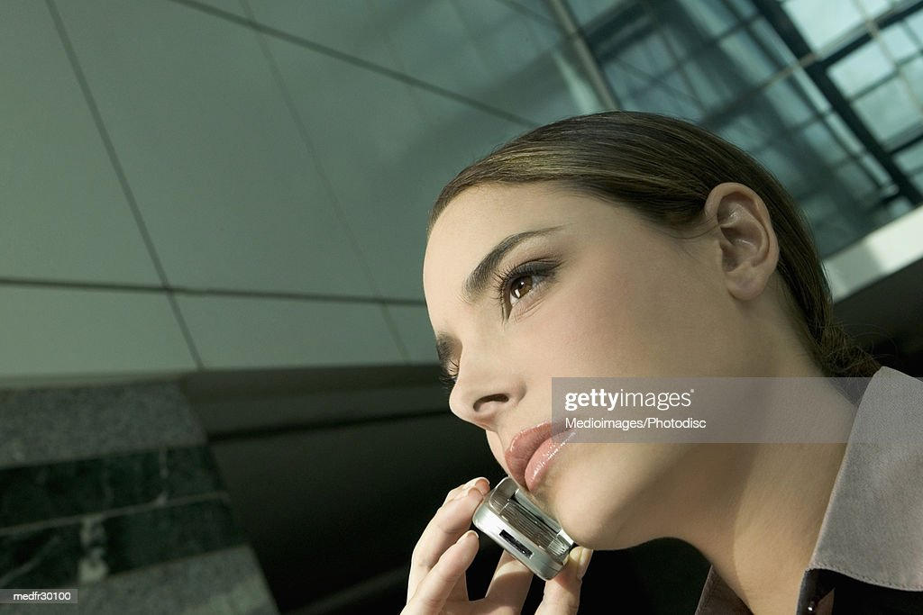 Serious young businesswoman talking on cell phone, close-up : Stock Photo