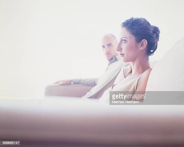 Serious young couple sitting on a sofa.