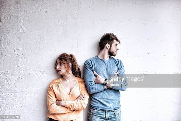 serious young french couple looking in opposite directions