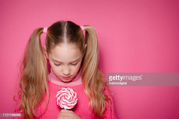serious young girl with lollipop shot against pink pastel background - lollipop stock pictures, royalty-free photos & images
