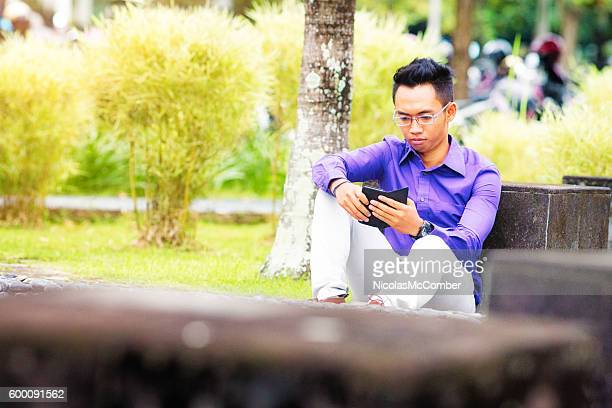 Serious young Indonesian male student looking at mobile phone