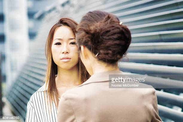 Serious young Japanese woman being scolded by her female boss