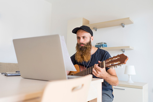 Serious young man at home with earphones and laptop playing guitar - gettyimageskorea