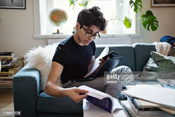 serious young man doing homework while sitting on sofa with mobile phone and laptop at home - distance learning stock pictures, royalty-free photos & images