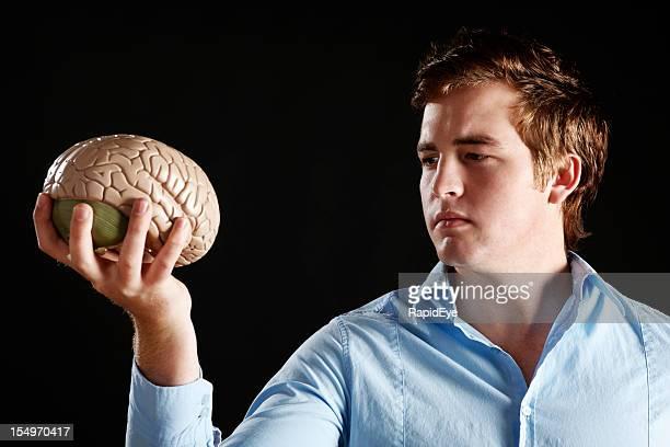 Grave giovane uomo tiene modello anatomico di un cervello umano