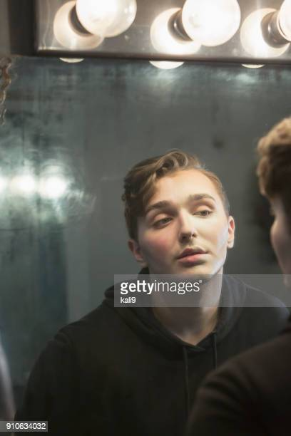 serious young man in dressing room staring at reflection - gender fluid stock photos and pictures