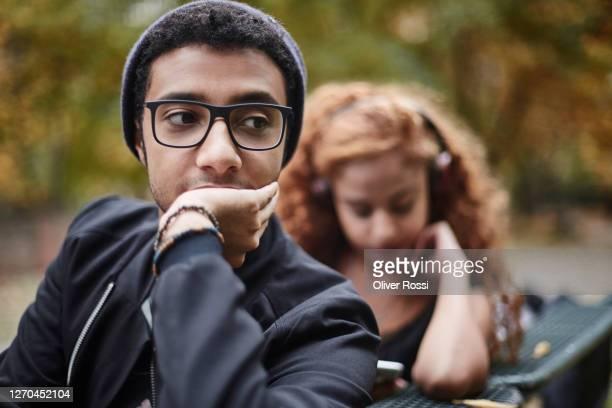 serious young man on park bench with girlfriend in background - zweifel stock-fotos und bilder
