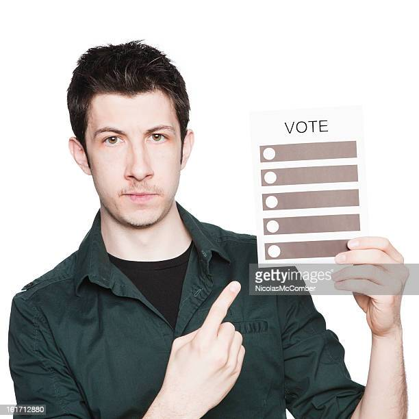 Serious young man points to voting ballot