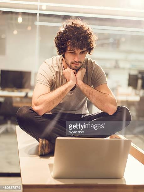Grave jeune homme assis à la table à l'aide d'un ordinateur portable.