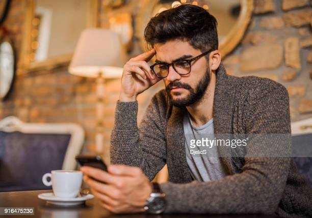 Serious young man studying from a phone in a coffee shop.