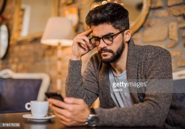 hombre joven serio estudiando desde un teléfono en una tienda de café. - fruncido fotografías e imágenes de stock