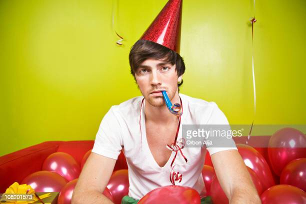 Serious Young Man Wearing Party Hat, Blowing Horn with Balloons
