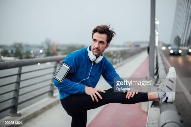橋の上を伸ばしてヘッドフォンでまじめな若者