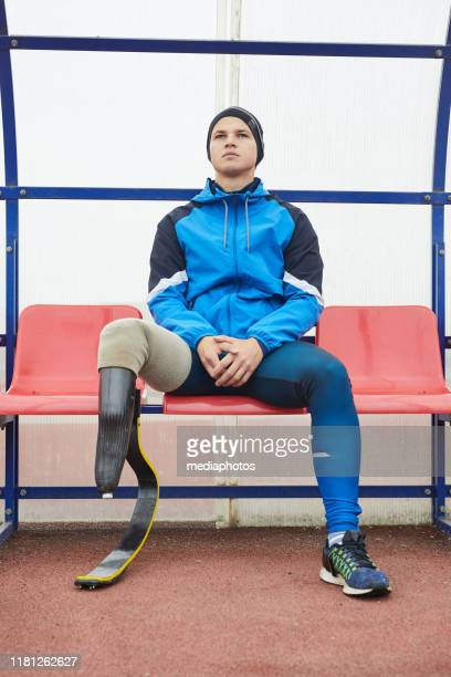 serious young motivated sportsman in blue jacket having running blade sitting on bench and looking into distance - sportsperson stock pictures, royalty-free photos & images