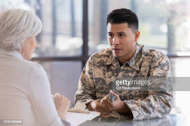 serious young soldier discusses issues with counselor - military doctor stock photos and pictures