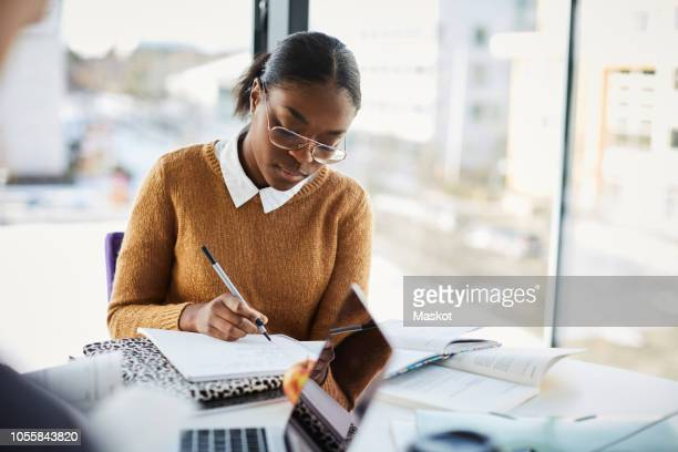 serious young student writing in book while studying at table in university - university stock pictures, royalty-free photos & images