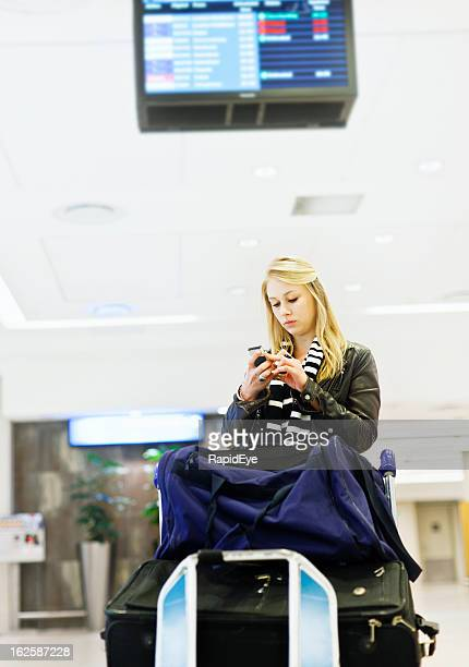 Serious young traveler at airport with luggage sends text