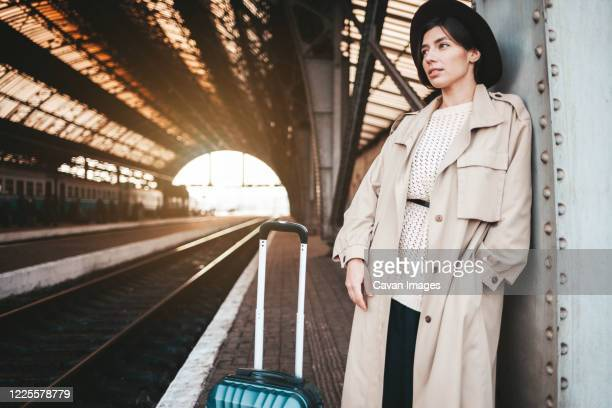 serious young woman at the railway station awaits the arrival of the t - trench coat stock pictures, royalty-free photos & images