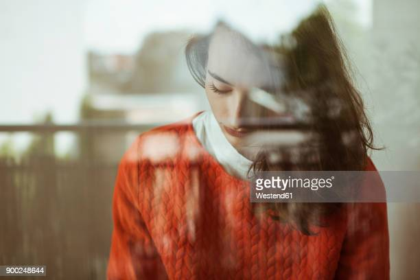 Serious young woman behind glass pane
