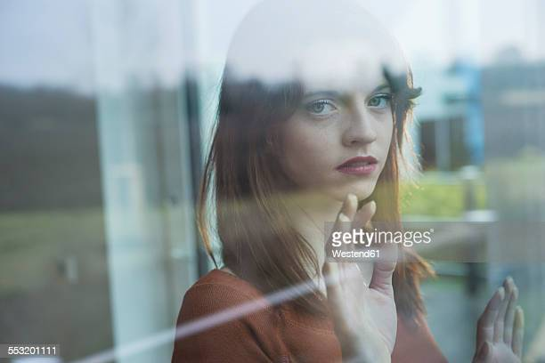 Serious young woman behind windowpane