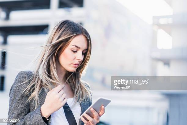 Serious young woman checking cell phone outdoors