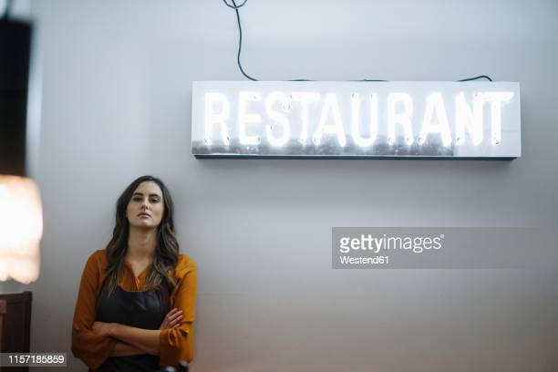 serious young woman leaning against a wall under restaurant neon light - unabhängigkeit stock-fotos und bilder