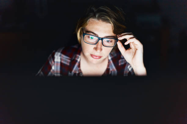 serious young woman, lit by monitor against black, adjusts spectacles - fraud job stock pictures, royalty-free photos & images