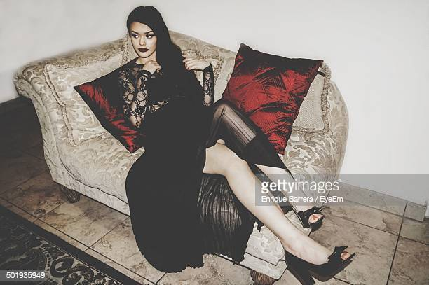 serious young woman looking away while sitting on couch - femme fatale stock photos and pictures