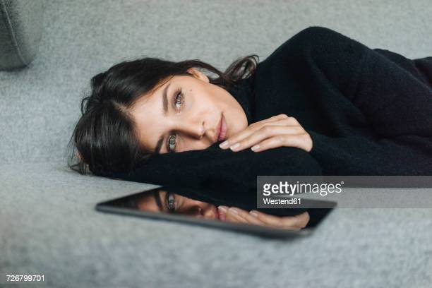 serious young woman lying on couch next to tablet - vestito nero foto e immagini stock