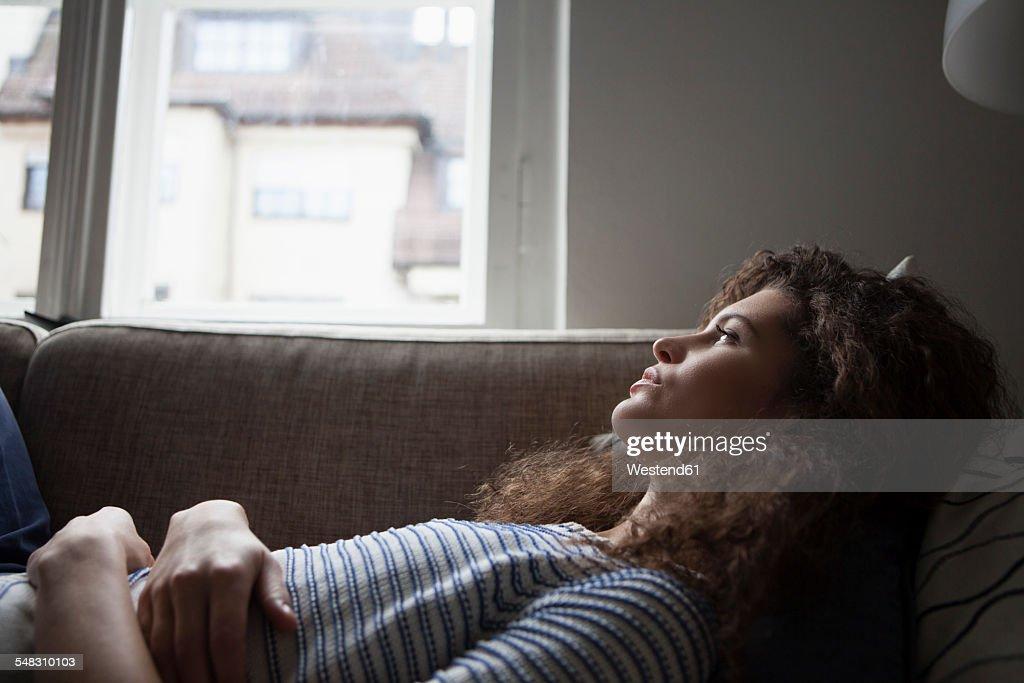 Serious young woman lying on sofa : Stockfoto