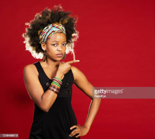 serious young woman pointing to the side - bangle stock pictures, royalty-free photos & images