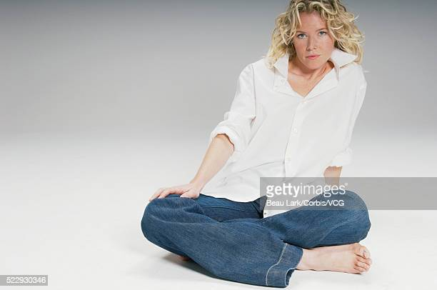 Serious young woman sitting cross-legged