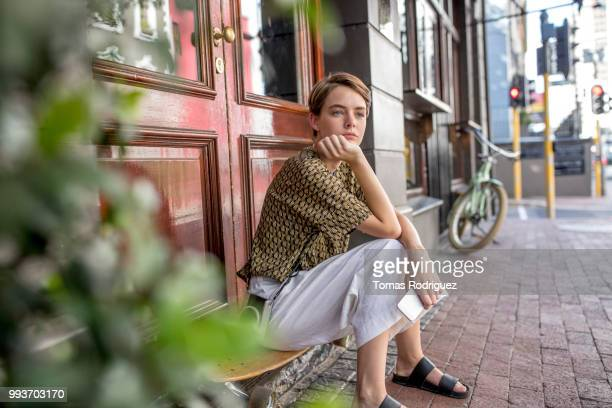 serious young woman sitting on skateboard at the door - waiting stock-fotos und bilder
