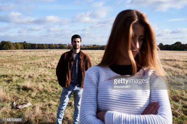 serious young woman standing on a field with man behind her - conflict stock pictures, royalty-free photos & images