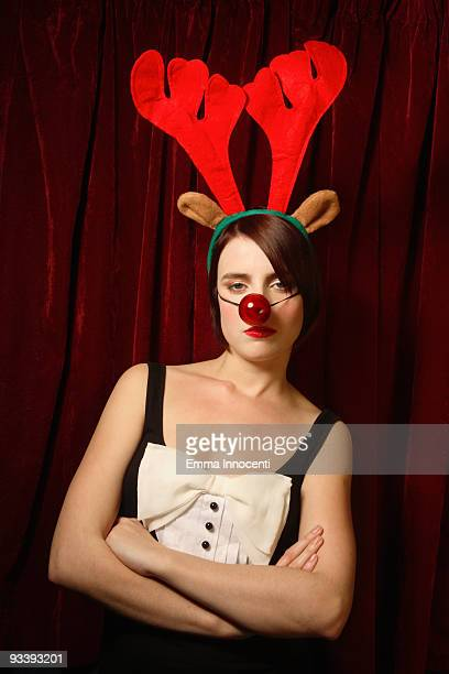 Serious young woman with reindeer antlers