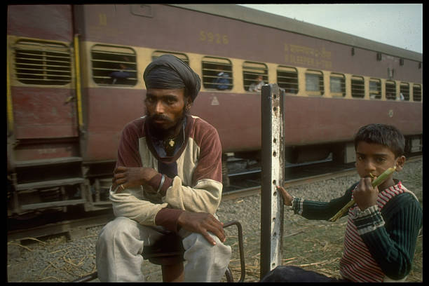 Seriousfaced Sikh man celery stalklike chewing boy poised in front of train in separatist Sikhtroubled Punjab