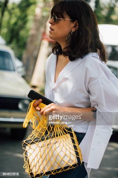 Serli Gazer Boyaci of Elle Turey wears The Jacquelyns white shirt and a yellow net bag with Balenciaga bag on May 4 2018 in Tbilisi Georgia