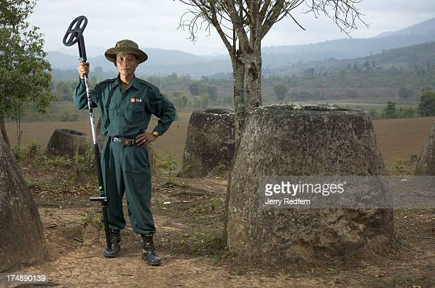 Serm Kham, a technician with the Mines Advisory Group in Laos, poses with a metal detector he used to find buried bombs around Site 3 at the Plain of...
