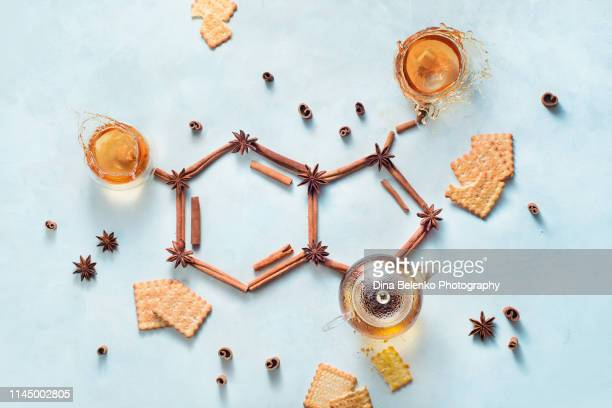 serotonin molecule made out of cinnamon and teacups with splashes. creative drink flat lay with the hormone of joy. - hormone stock pictures, royalty-free photos & images