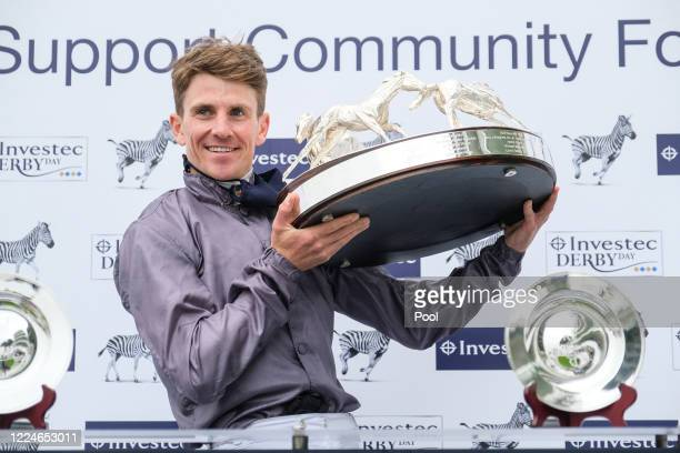 Serpentine and Emmet McNamara are presented the trophy after winning The Investec Derby at Epsom Racecourse on July 04 2020 in Epsom England The...
