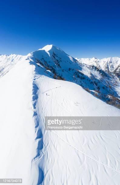 serpentine print in the fresh snow to climb with ski a mountain peak. - italia ストックフォトと画像