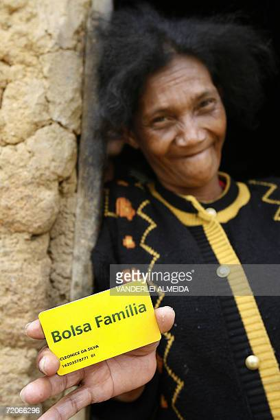Brazilian Cleonice da Silva mother of four and grandmother of four happily shows her 'Bolsa Familia' social plan card in Serra Azul north of the...