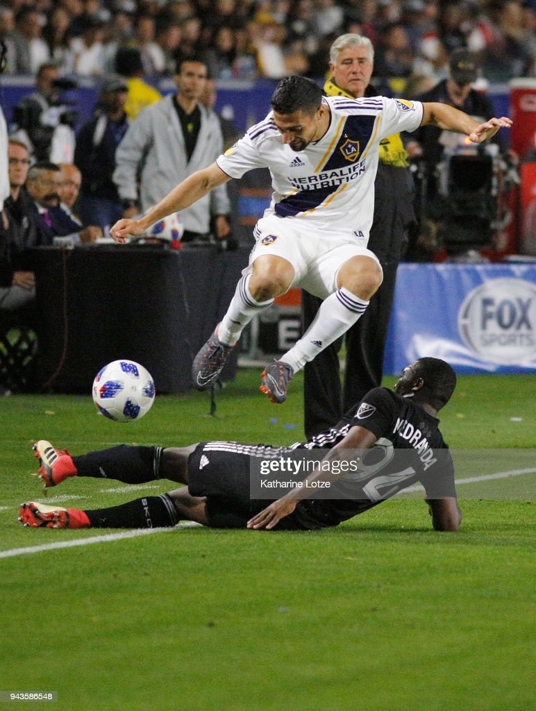 Servando Carrasco #14 of the Los Angeles Galaxy jumps over Jimmy Medrana #94 of Sporting Kansas City during a game at StubHub Center on April 8, 2018 in Carson, California.