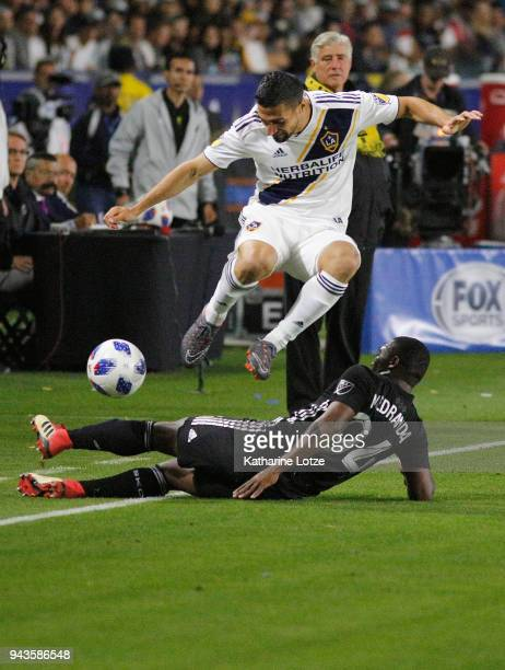 Servando Carrasco of the Los Angeles Galaxy jumps over Jimmy Medrana of Sporting Kansas City during a game at StubHub Center on April 8 2018 in...