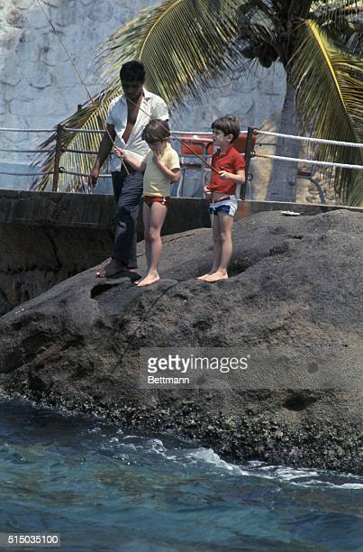 A servant baits hook as John F Kennedy Jr and his cousin Anthony Radziwill fish in the Pacific Ocean here March 19 Jacqueline Kennedy and her sister...