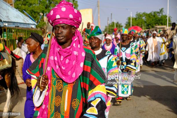 Servants dressed in colorful gala costumes marching through the streets of Gumel during a durbar celebration A durbar is a celebration in northern...