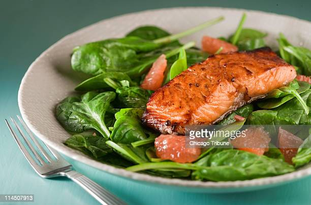 Serve guests a delicious perfectly glazed broiled salmon steak atop vinaigrettedressed spinach