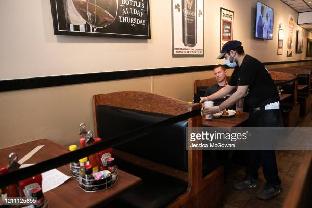 Server Anthony Mata waits on a customer during the first day back to dine-in service at Roasters on April 27, 2020 in Atlanta, Georgia. Roasters is...